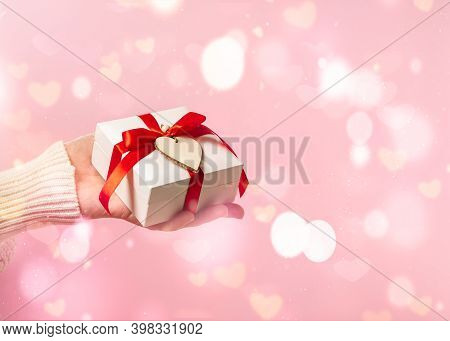 Beauty Woman Hands Holding Gift Box With Red Bow On Pink Glow Bokeh Background, Close-up. Pastel Col