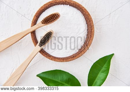 Two Wooden Bamboo Toothbrushes And Baking Soda On A White Background, Top View. Eco Friendly Toothbr