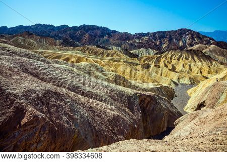 Picturesque multicolor sunset. Zabriskie Point in Death Valley, California, USA. Magnificent landscape and a variety of shades. The concept of active, extreme and photo tourism