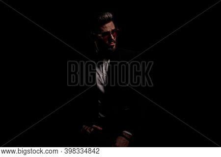 sexy young man in black velvet tuxedo looking to side and posing wit hands in pockets on black background in studio
