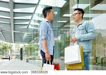 Young Asian Man Standing In The Street And Discussing Sales And Bargains During Black Friday