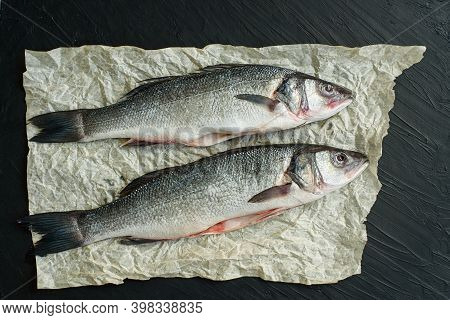 Raw Fish Seabass. Two Raw Fish Fillet On Paper Black Stone Background Ready For Cooking, Food Backgr