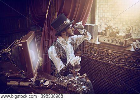 Adventure world of steampunk. Scientist steampunk man inventor looks through binoculars out the window from his laboratory. Victorian interior.