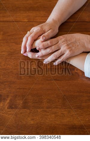 Elderly Mother And Her Daughter Holding Hands While Sitting At The Table.close Up On Women Of Differ