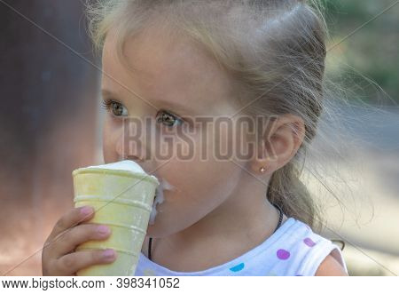 Portrait On A Blurred Background Of A Beautiful Girl Of Five Years Old With Big Eyes Eating Ice Crea