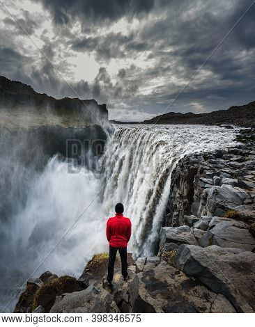 Young Hiker Standing Close To The Dettifoss Waterfall Located On The Jokulsa A Fjollum River In Icel