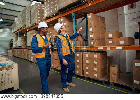 Male Worker Assisting His Supervisor For Checking The Stock In The Warehouse