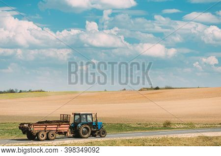 Tractor With Cart And Compost Moving On Country Road In Spring Season. Agricultural Landscape.