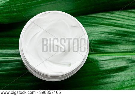 Moisturizing White Cream In Plastic Jar On Greenery Top View. Organic Cosmetics For Moisturizing And