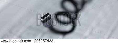 Close-up Of Black Cable For Connecting To Device Lies On White Computer Keyboard. Laptop Accessories