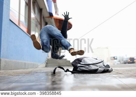 Man In Winter Dress Slip On Sidewalk With Ice Closeup Background. Heath Insurance Concept