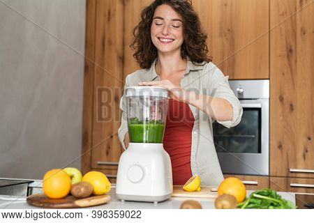 Happy woman making healthy fruit smoothies. Smiling young woman making healthy drink using blender with fresh vegetables. Girl making juice using juicer machine: wellness, diet and healthy eating.