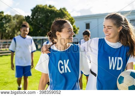 Two girls talking to each other after football training. Cheerful college players in conversation after sport match. Soccer players hugging and appreciating performance of the teammate after the match