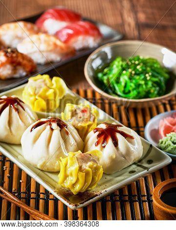 Assortment Of Japanese Sushi Set, Xiao Long Bao, Shaomoi, Nigiri, Gyozas Dumplings And Wakame Salad