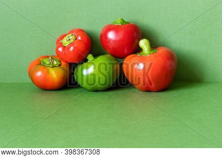 Bell Peppers Composition On A Green Background. Copy Space