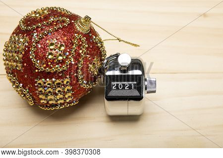 A Handheld Counter Showing 2021 Number With A Red Christmas Bauble On Wooden Background. 2021 New Ye