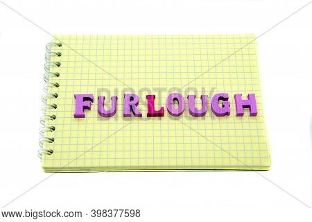 Word Furlough Laid Out Of Wooden Letters On Notebook With Yellow Grid Paper. Concept Of Job Loss Dur