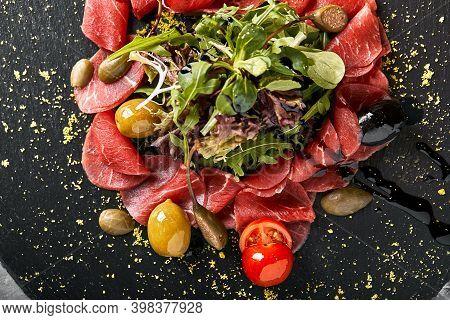 Beef Carpaccio With Arugula On A Black Plate, Traditional Italian Cuisine. Dark Key, Copy Space,