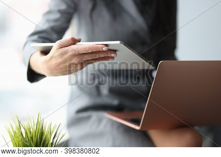Business Woman Holding Digital Tablet And Laptop In Hands In Office Closeup. Preparation For Seminar