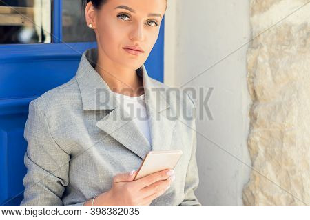 Portrait Of Fashionable Young Woman Using Smartphone Near The Door Outdoors.