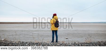 Wide Shot Backview Of A Young Woman Tourist With A Backpack Walking On Sideroad Among Vast Empty Win
