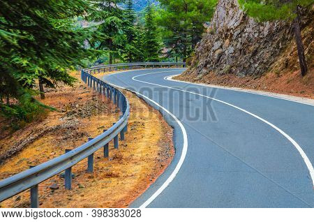 Asphalt Serpentine Road In Troodos Mountain Range With Roadside Fence And Trees, Cyprus
