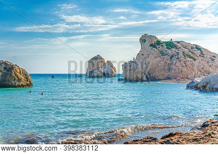 Aphrodite Beach With Stone Rocks In Aphrodite Bay Of Mediterranean Sea Water, Blue Sky In Sunny Day