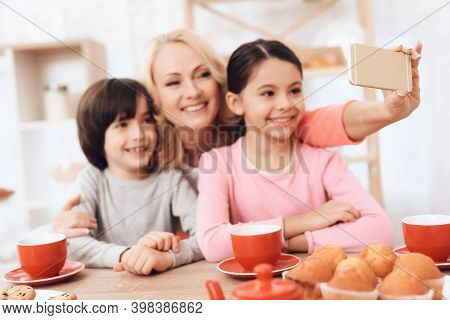 Adult Beautiful Woman Makes Selfie On Smartphone With Her Grandchildren Who Drink Tea At Kitchen.