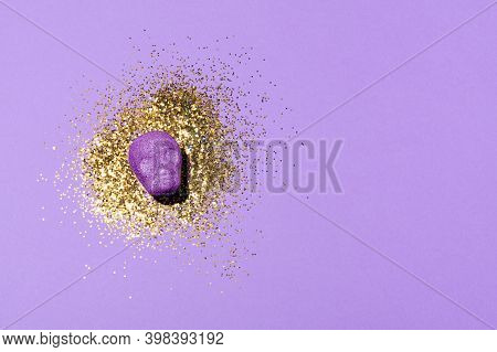 Purple Sugary Candy Skull On A Lilac Background With Golden Glitter. Minimal Halloween Concept