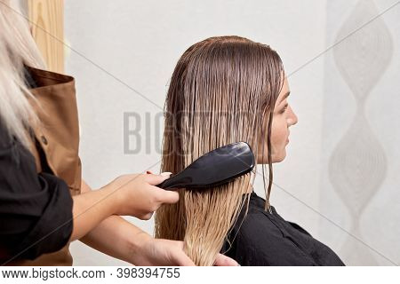 A Female Hairdresser Combs The Clients Blonde Hair With A Comb.