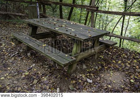Old Picnic Bench On The Mountain Path. Old And Rotten Wood From The Rain. No Maintenance.