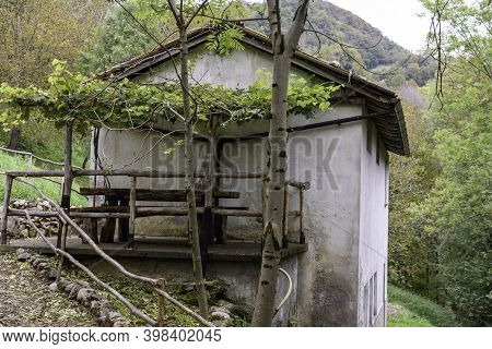 Old Mountain House With Wooden Table And Benches For Lunch. Remains Of Ancient Houses Used As Second
