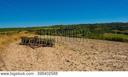 San Quirico D'orcia, Italy - September 3rd 2020. A Harrow Disc Plough In The Late Summer Landscape I