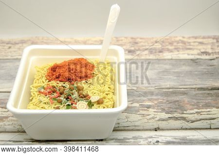 Instant Dryed Noodles With Dry Vegetables And Spices With Red Pepper In Disposable Container With Pl