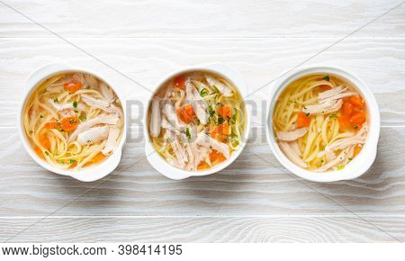 Three White Bowls With Warm Healthy Homemade Chicken Soup On Cutting Board, White Wooden Table Backg