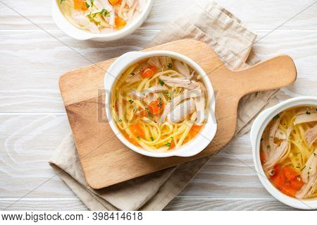 Warm Healthy Homemade Chicken Soup In White Ceramic Bowls On Cutting Board, White Wooden Table Backg