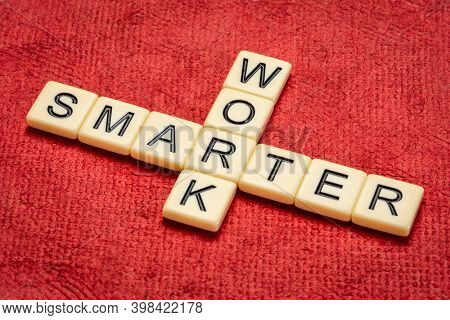 work smarter crossword in ivory letter tiles against textured handmade paper, business, productivity, efficiency and personal development concept