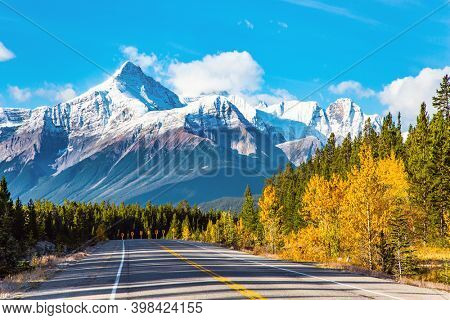 Indian summer in the Canadian Rockies. The sharp peaks of the Rocky Mountains are clearly visible against the blue sky. The asphalt highway goes into the distance