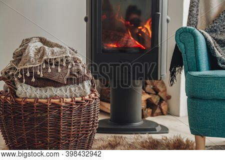 A Stack Of Warm Clothes In A Wicker Basket An Iron Fireplace Wit