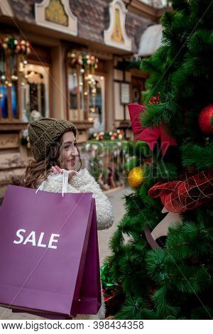 Happy Girl Holds Paperbags With Symbol Of Sale In The Stores With Sales At Christmas, Around The Cit