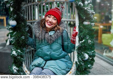 Young Beautiful Caucasian Girl Dressed In A Warm Winter Jacket, Knitted Hat And Gloves Sits On Chris