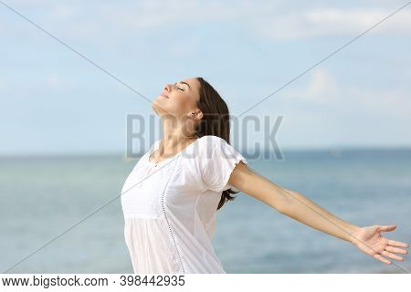 Relaxed Woman Breathing Fresh Air And Spreading Stretching Arms On He Beach