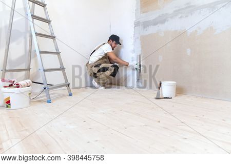 Male Painter With A Putty Knife In His Hands Makes Repairs In Th