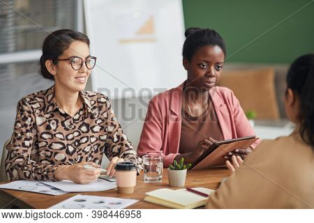 Portrait Of Multi-ethnic All Female Business Team Discussing Project While Sitting At Meeting Table