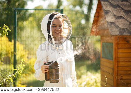 Beekeeper Girl In White Suit Posing Near A Clue With A Bee Smoker.
