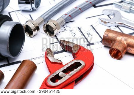 Plumbing Tools And Faucet On A Blueprint Project In Close-up