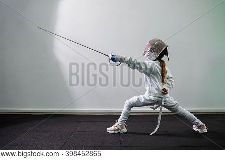Children Lunge On Swords. A Child In A Class At A Fencing School