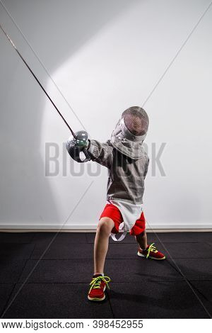 A Child In A Fencing Costume Is Holding An Epee. Girl Learning Fencing