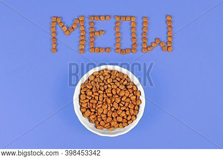 Bowl With Dry Cat Food And Kibbles Forming Word 'meow' On Purple Background