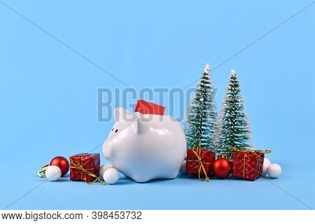 Concept For Christmas Gift Voucher Giving And Savings Showing White Piggy Bank With Red Coupon Surro